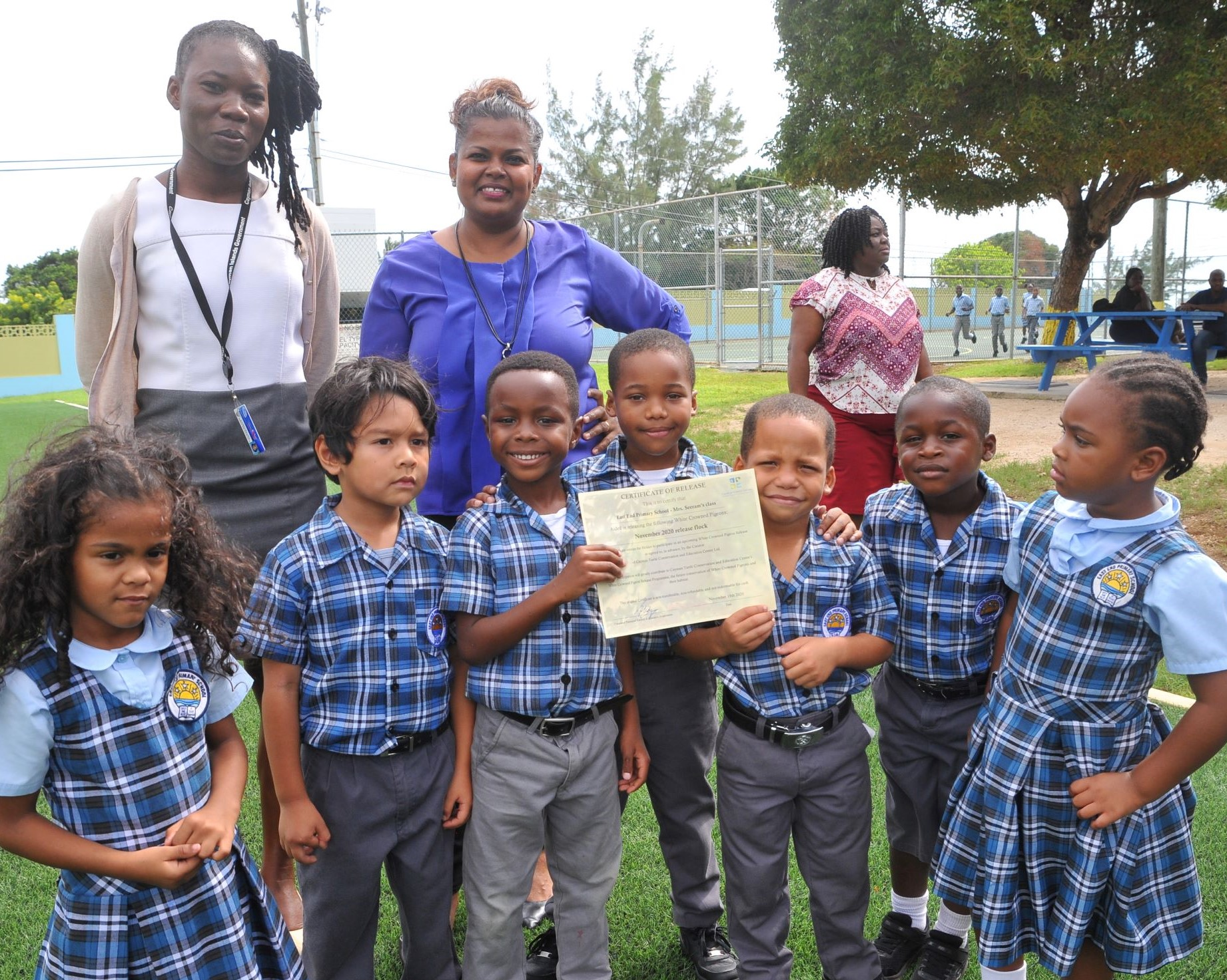 Year One teachers Ms. Seeram, and Kedeen Foster with their class, and their pigeon-release certificate